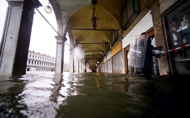 A Carabinieri police officer (R) holding his transparent plexiglass anti-riot shield walks across a flooded arcade by St. Mark's Square on November 15, 2019 in Venice, two days after the city suffered its highest tide in 50 years (Filippo MONTEFORTE / AFP)