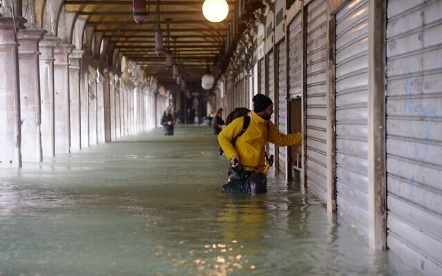 A man stands by a closed shop in a flooded arcade by St. Mark's square on November 15, 2019 in Venice, two days after the city suffered its highest tide in 50 years  ( Filippo MONTEFORTE / AFP)