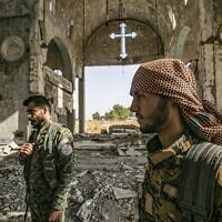 Members of the Khabour Guards (MNK) Assyrian Syrian militia, affiliated with the Syrian Democratic Forces (SDF), walk in the ruins of the Assyrian Church of the Virgin Mary, which was previously destroyed by Islamic State (IS) group fighters, in the village of Tal Nasri south of the town of Tal Tamr in Syria's northeastern Hasakah province on November 15, 2019. (Delil souleiman / AFP)