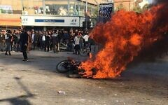 Iranian protesters gather around a burning motorcycle during a demonstration against an increase in gasoline prices in the central city of Isfahan, on November 16, 2019. (AFP)