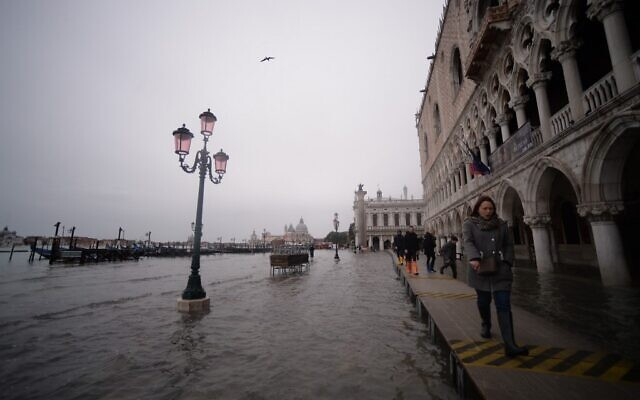 Visitors walk in flooded Venice, in the morning of November 17, 2019. (Photo by Filippo MONTEFORTE / AFP)