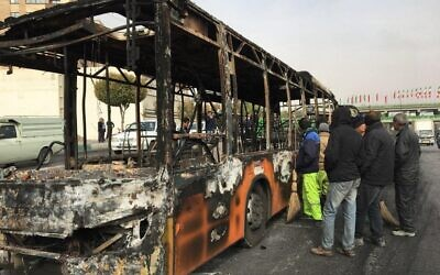 Iranians inspect the wreckage of a bus that was set ablaze by protesters during a demonstration against a rise in gasoline prices in the central city of Isfahan on November 17, 2019. (AFP)