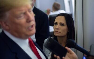 In this file photo taken on August 8, 2019, White House Press Secretary Stephanie Grisham listens as US President Donald Trump speaks to the media aboard Air Force One while flying between El Paso, Texas and Joint Base Andrews in Maryland. (Photo by SAUL LOEB / AFP)