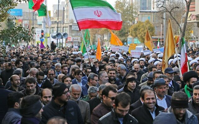 """Iranians wave national flags during a protest in support of the Islamic Republic's government and supreme leader, Ayatollah Ali Khamenei, in the northwestern city of Ardabil on November 20, 2019, as President Hassan Rouhani says the country's people had defeated an """"enemy conspiracy"""" behind a wave of violent street protests. (STR/AFP)"""