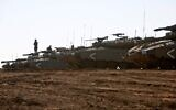 An Israeli soldier stands on a Merkava tank deployed on the Golan Heights on November 20, 2019. (JALAA MAREY / AFP)