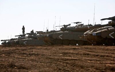 An Israeli soldier stands on a Merkava tank deployed on the Golan Heights on November 20, 2019. (JALAA MAREY / AFP)
