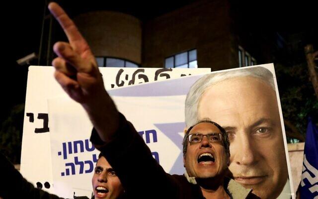 Os apoiadores do primeiro-ministro israelense Benjamin Netanyahu cantam slogans enquanto demonstram solidariedade com ele fora de sua residência oficial em Jerusalém, em 21 de novembro de 2019 (GALI TIBBON / AFP)