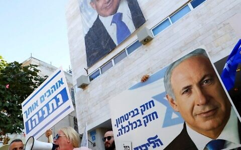 Supporters of Prime Minister Benjamin Netanyahu chant slogans and hold up signs in support of him during a counter-rally outside the Likud party headquaters in the coastal Mediterranean city of Tel Aviv on November 22, 2019, as Labour Party supporters demonstrate against him nearby. (Jack Guez/AFP)