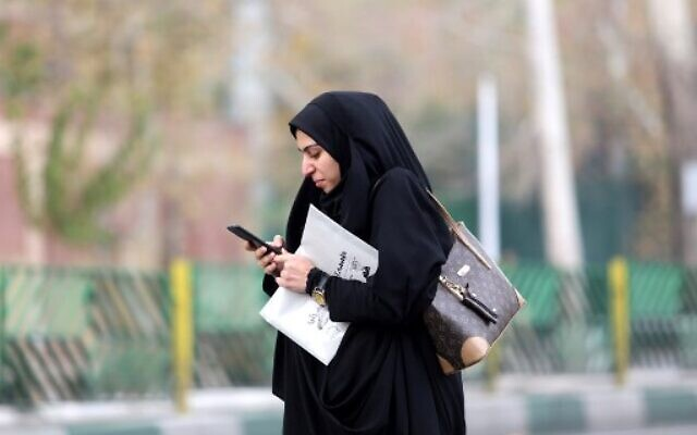 A woman uses a smartphone while standing on a street in the Iranian capital Tehran on November 23, 2019. (ATTA KENARE/AFP)