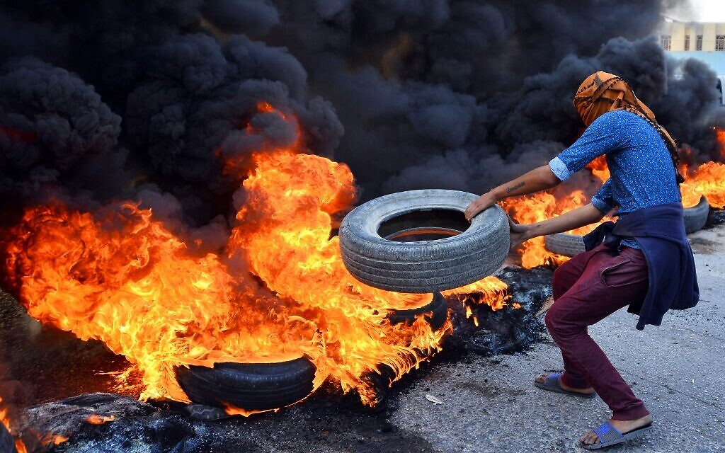 An Iraqi protester throws a tire on a stack of burning tires at a roadblock in the central holy shrine city of Najaf on November 26, 2019. (Haidar HAMDANI / AFP)