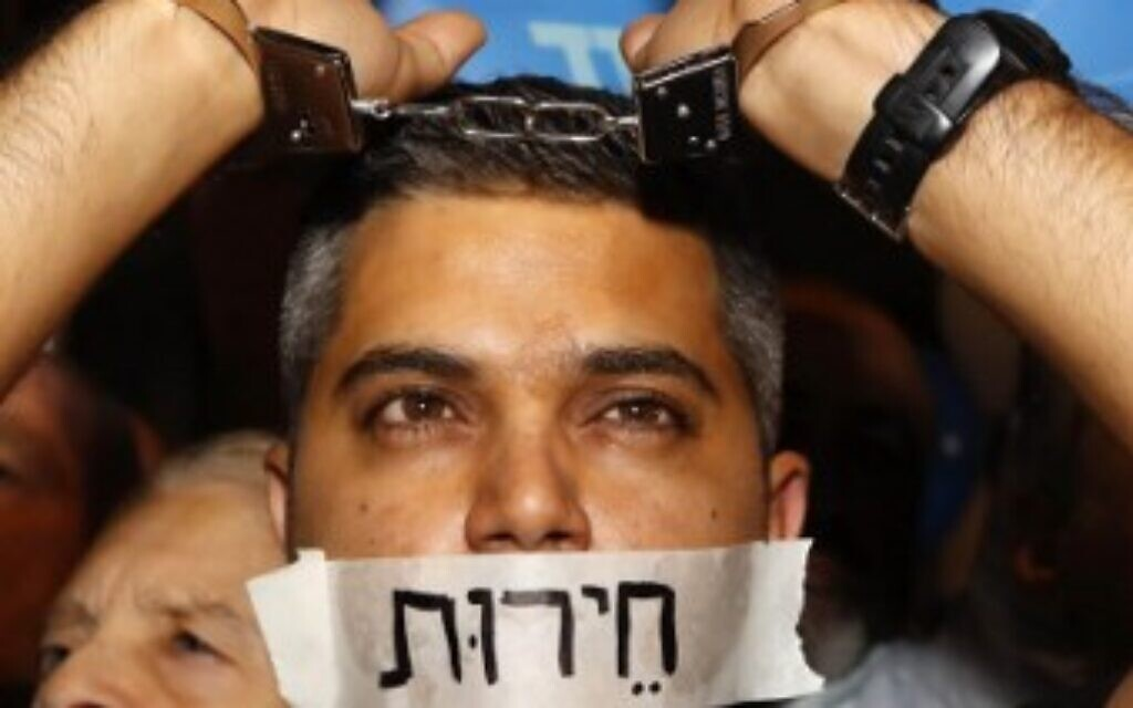 """A supporter of Prime Minister Benjamin Netanyahu wearing handcuffs and covering his mouth with a sign reading in Hebrew: """"freedom,"""" at a rally held under the banner 'protesting the coup' in Tel Aviv, on November 26, 2019. (Jack Guez/AFP)"""
