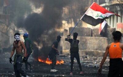 An Iraqi anti-government protester waves a national flag close to a concrete barricade amidst clashes with security forces along the capital Baghdad's Rasheed street near al-Ahrar bridge on November 29, 2019 (AHMAD AL-RUBAYE/AFP)