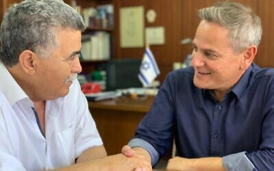 Labor chairman Amir Peretz (L) shakes hands with Meretz (and later Democratic Camp) chairman Nitzan Horowitz on July 17, 2019. (Courtesy)