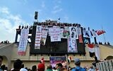 In this photo from October 30, 2019, Iraqi anti-government protesters hang their demands and slogans while standing on a building near Tahrir Square, Baghdad, Iraq. (AP Photo/Hadi Mizban)