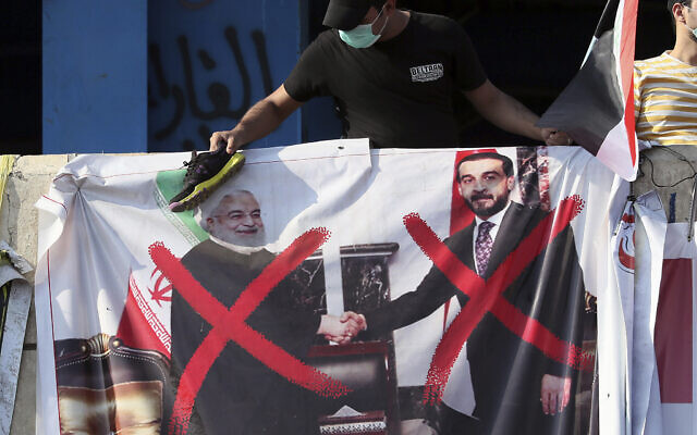 A poster of Iraq Parliament Speaker Mohammed al-Halbousi, right, and Iran President Hassan Rouhani, left, hang on a building near Tahrir Square, during ongoing protests in Baghdad, Iraq, November 6, 2019. (AP Photo/Hadi Mizban)