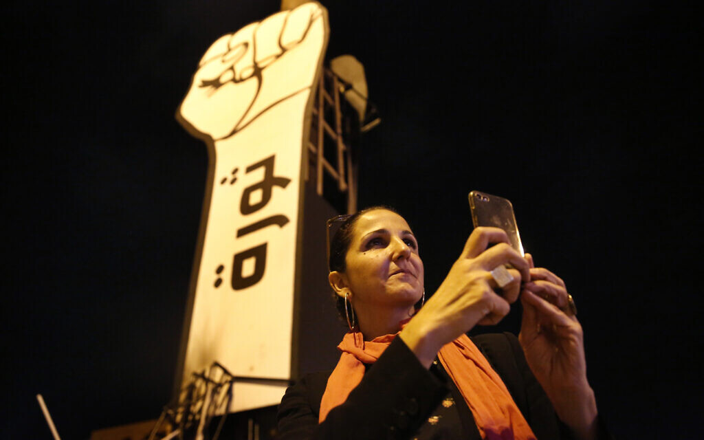 Singer Tania Saleh takes pictures with her mobile phone at the martyrs square where the ongoing anti-government take place everyday, in downtown Beirut, Lebanon, November 8, 2019 (AP Photo/Hussein Malla)