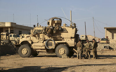 In this photo from February 23, 2017, US Army soldiers stand outside their armored vehicle on a joint base with Iraqi army south of Mosul, Iraq. (AP Photo/ Khalid Mohammed, File)