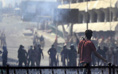 Iraqi riot police fire tear gas to disperse anti-government protesters gathering on bridge in central Baghdad, Iraq, November 9, 2019. (AP Photo/Hadi Mizban)