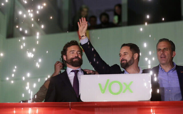 Santiago Abascal, leader of far-right Vox Party, waves to supporters as fireworks go off outside the party headquarters after the announcement of the general election first results, in Madrid, Sunday, Nov. 10, 2019. (AP Photo/Andrea Comas)
