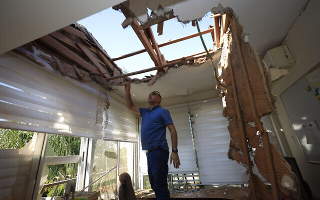 A man looks at the damage to a house in Sderot, Israel, after it was hit by a rocket fired from Gaza Strip, Nov. 12, 2019. (AP Photo/Tsafrir Abayov)