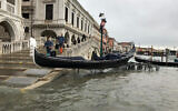 A gondola boat is stranded atop a bike rack after high tide in Venice, Italy, November 13, 2019.  (Alessandra Rallo/AP)