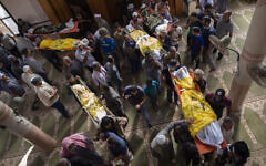 Palestinian mourners carry out the bodies of Rasmi Abu Malhous and seven members of his family who were killed in overnight Israeli missile strikes that targeted their house, during their funeral at a mosque in Deir al-Balah, central Gaza Strip,, November 14, 2019. (AP Photo/Khalil Hamra)