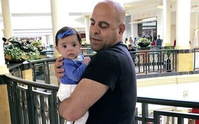 In this June 2016 photo provided by Guila Fakhoury, her father Amer Fakhoury holds his granddaughter, Kira, in King of Prussia, Pennsylvania. (Guila Fakhoury via AP)