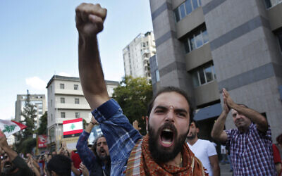 In this October 29, 2019 file photo, an anti-government protester shouts slogans after he is attacked by Hezbollah supporters, in Beirut, Lebanon. (AP Photo/Hussein Malla, File)