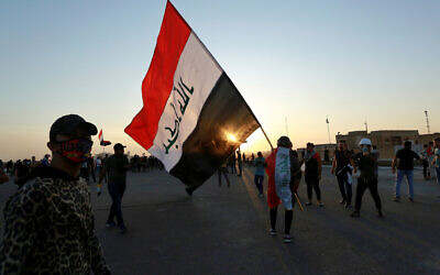 People walk through Khilani Square after protesters took control and reopened it after clashes between Iraqi security forces and anti-government demonstrators in Baghdad, Iraq, November 16, 2019. (AP Photo/Hadi Mizban)