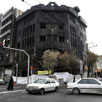 Traffic passes a building that was set ablaze during recent protests over government-set gasoline prices rises, in Tehran, Iran, November 20, 2019. (Ebrahim Noroozi/AP)