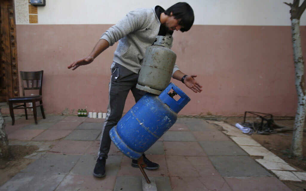 In this Nov. 20, 2019, photo, Mohammed al-Shenbari demonstrates to balance objects using what he calls a mix of mind and body, in the yard of his home in Beit Hanoun, northern Gaza Strip. (AP Photo/Hatem Moussa)