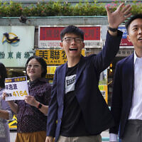 Election winner candidate Kelvin Lam, right, and pro-democracy activist Joshua Wong, second right, wave to people and thank for their support, outside South Horizons Station in Hong Kong, Monday, Nov. 25, 2019. (AP Photo/Vincent Yu)