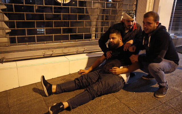 Anti-government protesters comfort a a person hit by tear gas during a clash between supporters of the Shiite Hezbollah and Amal groups and the demonstrators, in Beirut, Lebanon, early Monday, Nov. 25, 2019. Security forces fired tear gas amid confrontations in central Beirut that went into Monday morning between Hezbollah supporters and demonstrators protesting against Lebanon's political elite. (AP Photo/Hussein Malla)