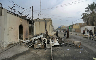 Security forces and civilians gather near the burned Iranian consulate in Najaf, Iraq, Thursday, Nov. 28, 2019. (AP Photo/Anmar Khalil)