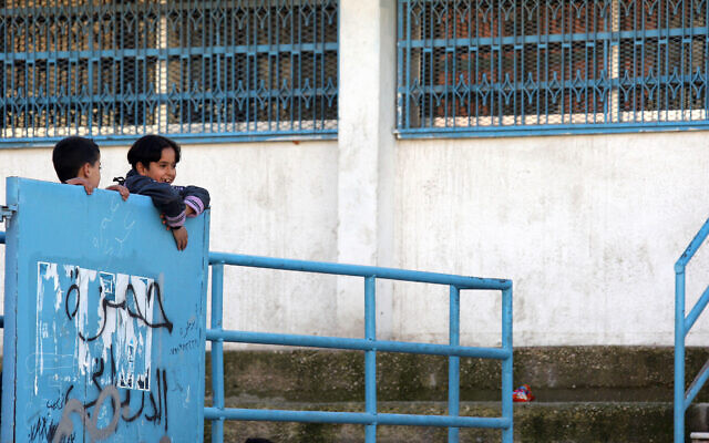 Two boys climb their UNRWA school's gate in Al Nasr refugee camp in Amman, Jordan Feb. 1, 2010, after the end of the first day of the second semester of the school year (AP Photo/Mohammad Abu Ghosh)