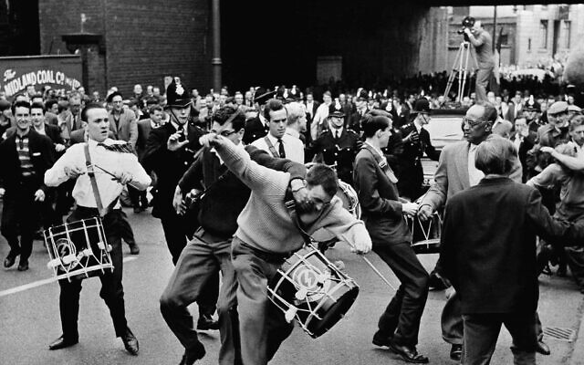 An irate spectator attacks a drummer of British fascist leader sir Oswald Mosley, leader of the extremist right-wing British union movement, during a march through Manchester, England on July 29, 1962. Rocks and tomatoes were hurtled towards some 40 marchers before they were physically attacked by the crowd. (AP Photo)