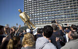 People watch a statue of Prime Minister Benjamin Netanyahu as it falls at Rabin square in Tel Aviv, Israel, Tuesday, Dec. 6, 2016. (AP Photo/Oded Balilty)
