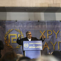 Nikos Michaloliakos, leader of Greece's extreme right Golden Dawn party, delivers a speech during a rally commemorating a 1996 military incident which cost the lives of three Greek navy officers and brought Greece and Turkey to the brink of war, in Athens, on Saturday, Feb. 3, 2018. (AP Photo/Yorgos Karahalis)
