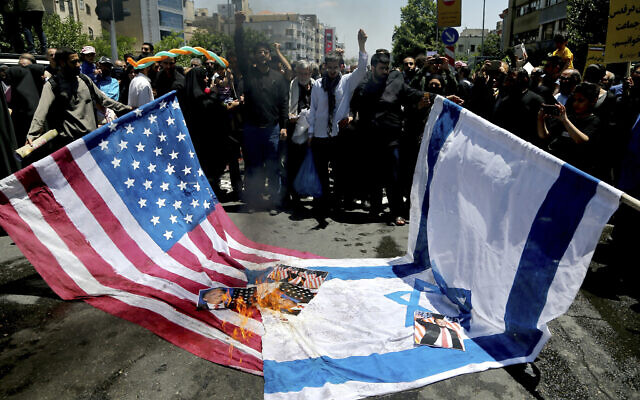 Iranian protesters burn Israeli and US flags in their annual anti-Israeli Al-Quds, Jerusalem, Day rally in Tehran, Iran, June 8, 2018. (AP/Ebrahim Noroozi)