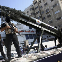 Palestinian members of the Al-Quds Brigades, the military wing of the Islamic Jihad terrorist group, parade with a replica rocket on a truck during a march to show loyalty for the Iranian-backed Palestinian movement's newly-elected leader Ziad al-Nakhalah during a rally along the streets of Gaza, Thursday, Oct. 4, 2018. (AP Photo/Adel Hana)