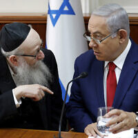 Benjamin Netanyahu, right, listens to Yaakov Litzman at the start of the the weekly cabinet meeting at the prime minister's office in Jerusalem,  January 6, 2019. (Gali Tibbon/Pool via AP)