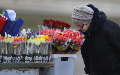 A woman smells the flowers at a street market on the eve of the International Women's Day in Minsk, Belarus on March 7, 2019. (AP Photo/Sergei Grits)
