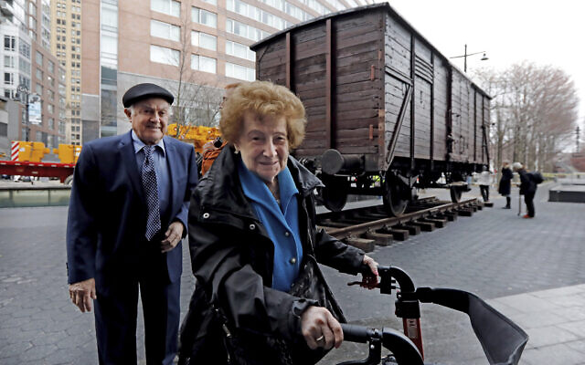 Holocaust survivors Leon Kaner, age 94, and his wife Ray Kaner, age 92, pass a vintage German train car, like those used to transport people to Auschwitz and other death camps, outside the Museum of Jewish Heritage, in New York, March 31, 2019. (AP Photo/Richard Drew)