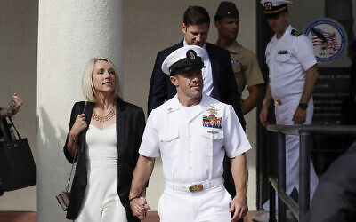 Navy Special Operations Chief Edward Gallagher, center, walks with his wife, Andrea Gallagher, as they leave a military court on Naval Base San Diego, Tuesday, July 2, 2019, in San Diego. A military jury acquitted the decorated Navy SEAL Tuesday of murder in the killing of a wounded Islamic State captive under his care in Iraq in 2017. (AP Photo/Gregory Bull)