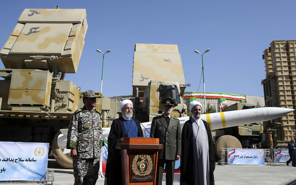 President Hassan Rouhani, second left, speaks during a ceremony to unveil the Iran-made Bavar-373, a long-range surface-to-air missile system, displayed at rear, as his Defense Minister Gen. Amir Hatami, second right, commander of army's air defense force Gen. Alireza Sabahifard, left, and the chairman of the parliament's National Security and Foreign Policy Committee Mojtaba Zolnour, listen, at an undisclosed location in Iran, August 22, 2019. (Iranian Presidency Office via AP)