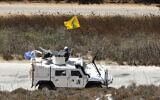 Spanish UN peacekeepers patrolling along the Lebanese-Israeli border pass a Hezbollah flag, in the southern Lebanese village of Kfar Kila, September 2, 2019. (AP Photo/Hussein Malla)