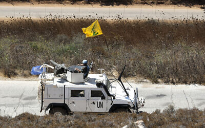 Spanish UN peacekeepers patrolling along the Lebanese-Israeli border pass a Hezbollah flag, in the southern Lebanese village of Kfar Kila, September 2, 2019. (AP Photo/Hussein Malla)