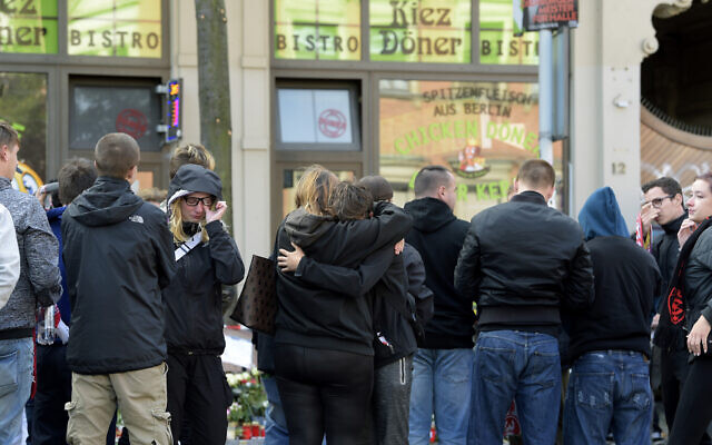 People mourn in front of a kebab grill in Halle, Germany, Thursday, October 10, 2019. (AP Photo/Jens Meyer)