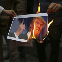 In this May 9, 2018, file photo, Iranian demonstrators burn a picture of US President Donald Trump during a protest in front of the former US Embassy in Tehran, Iran. (AP Photo/Vahid Salemi, File)