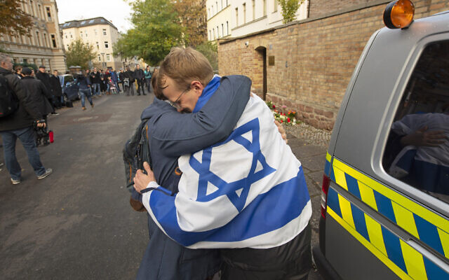 A person with a flag of Israel hugs another person in front of a synagogue in Halle, Germany, October 10, 2019. (AP Photo/Jens Meyer)